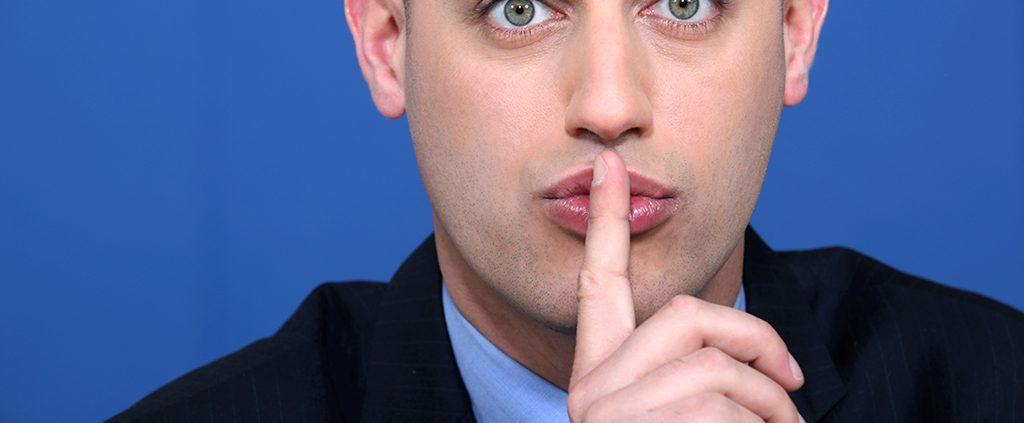 Geheimhaltung - Gesicht mit Finger vor schweigendem Mund